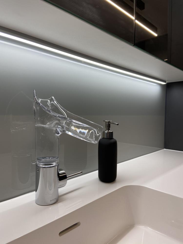 Gelakte glazen spatwand in de badkamer en een glazen kraan.