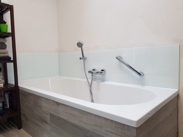 een gelakte glazen spatwand rond het bad beschermt de muren tegen het vocht