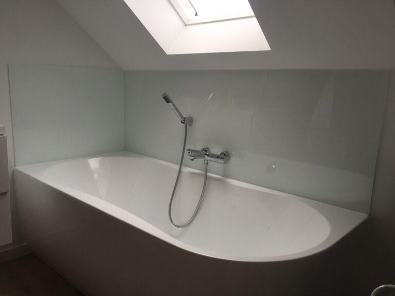 een gelakte glazen spatwand achter het bad beschermt de muren tegen het vocht