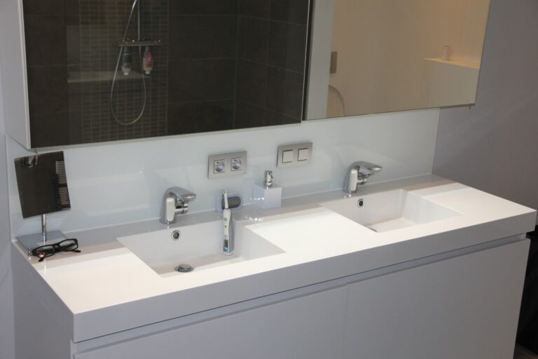een glazen spatwand achter de lavabo's beschermt de muren