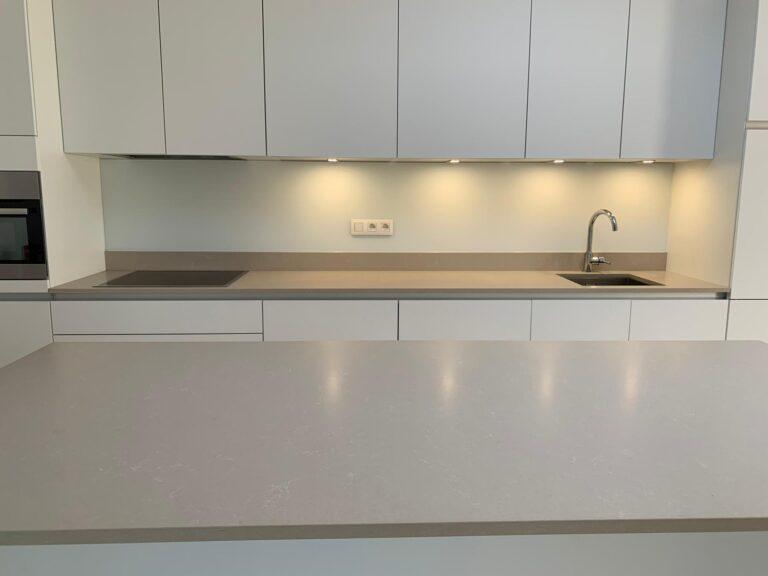 grijs gelakte glazen spatwand in moderne keuken