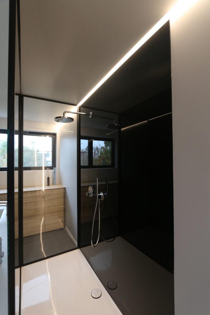 Badkamer: douchewanden en gelakte glaswanden.