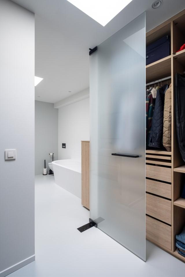 open matglazen pivoterende deur naar de badkamer