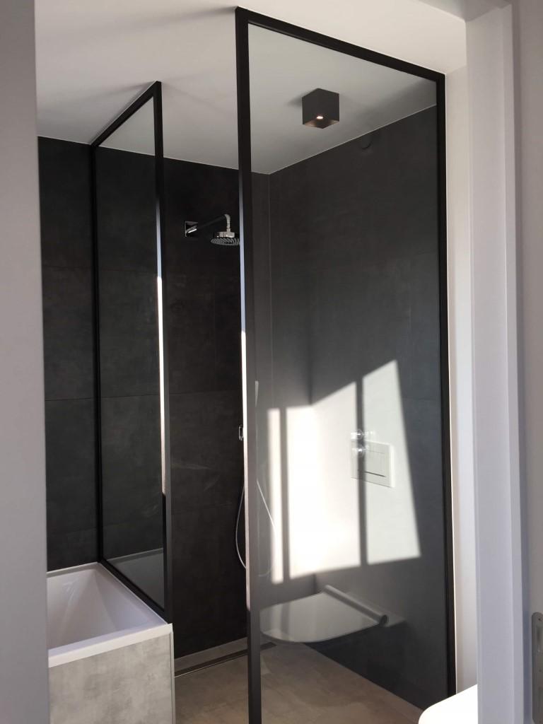 Douchewand, plafondhoog, met zwart gelakte profielen.