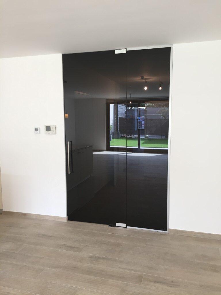 Zwarte pivoterende deur, in 2 richtingen openend & zelfsluitend, op een voetveer