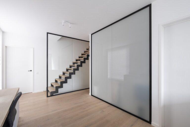 Een glazen wand als balustrade naast de trap en een glazen wand in verzuurd glas laat daglicht in de badkamer.