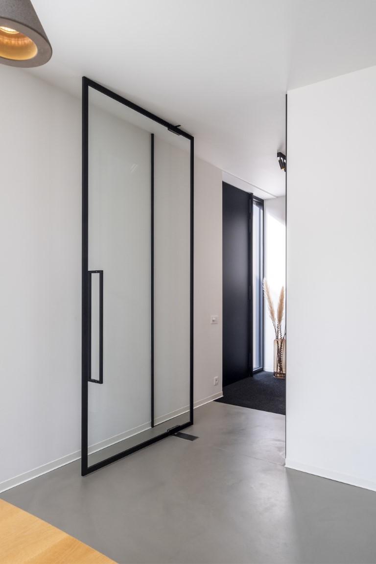 glazen deur in steellook met fijne profielen op de muren voor perfecte aansluiting