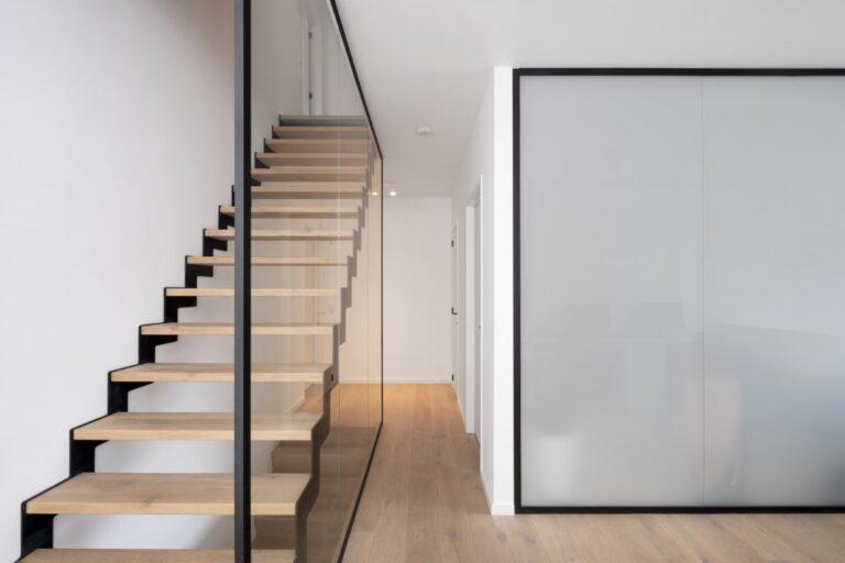Een glazen wand als balustrade naast de trap en een glazen wand in verzuurd glas voor de badkamer.